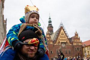 Мальчик в костюме короля сидит на плечах папы